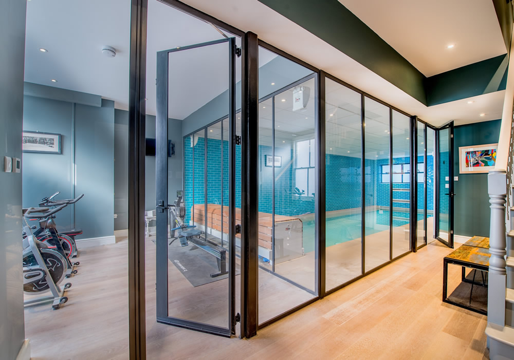 Steel windows used to separate a gym and indoor pool